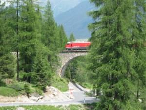 """De """"Rätische Bahn"""" in het Albuladal kruipt langzaam en zigzaggend door het dal omhoog."""