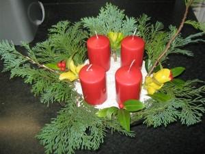 Een adventskrans kan ook gemaakt worden in een glazen schaaltje met wat zilverzand of kiezel, wat groen en vier mooie, rode kaarsen.