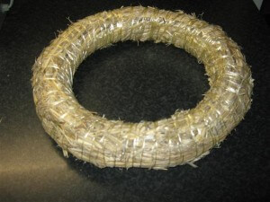 De adventskrans kan als ondergrond best wat stevigheid gebruiken in de vorm van een krans van stro, die voor weinig geld in de winkels te krijgen is.
